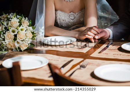 man's and woman's hands on the table in cafe