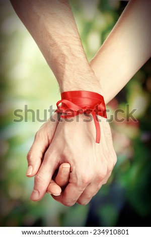 Man's and woman's hands tied with ribbon on bright background - stock photo