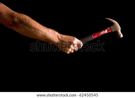 man's arm with hammer, isolated on black - stock photo