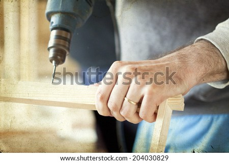 Man's arms drill lath in the workshop - vintage photo - stock photo