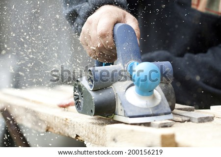 Man's arms sawing wood board in the workshop. - stock photo