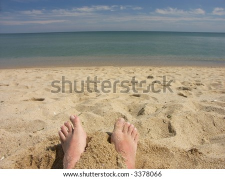 Man's bare feet protruding from sand on the beach facing the sea - stock photo