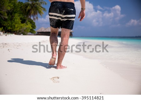 Man's bare feet walking at white sand beach. Picturesque landscape. Blue sky, coconut palms, white sand and azure water. Muscular legs walking on the beach. Leaving footprints on sand. Maldives.