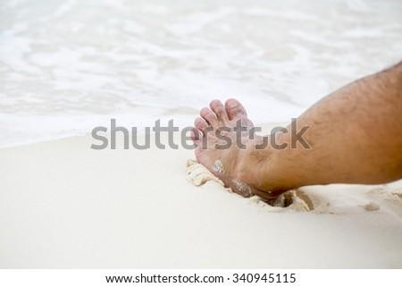 Man's bare foot on the Caribbean beach. - stock photo