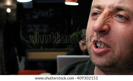 Man's emotional close portrait with big expressive eyes significant nose and small stubble beard. Dialog friendly conversation scene.  - stock photo