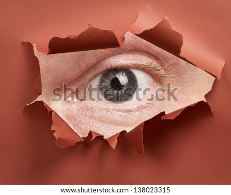Man's eye spying through hole in paper - stock photo