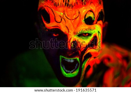 Man's face with fluorescent body art. Black background.