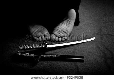 Man`s feet and ritual sword in black and white - stock photo