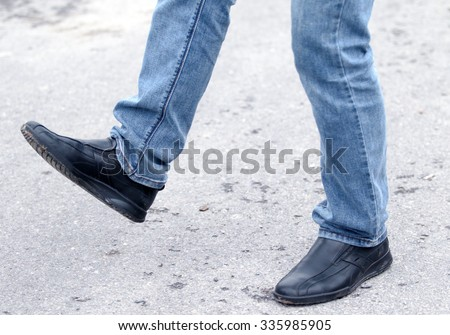 Man's feet in blue jeans in shoes close up, set in motion