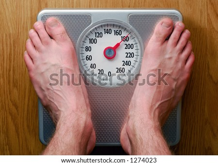 Man's Feet Standing on Bathroom Scale - stock photo