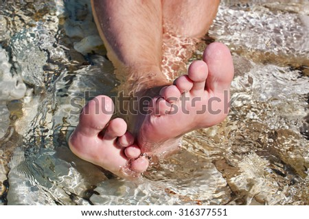 Man's foots in sea water at summer day - stock photo