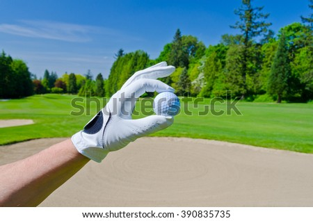 Man's, golfer hand holding golf ball with beautiful golf course as a background. - stock photo