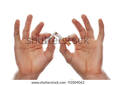 Man's hand breaking a cigarette - stock photo