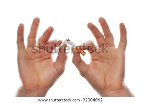Man's hand breaking a cigarette - stock photo