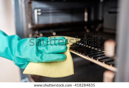 Man's hand cleaning the kitchen oven - stock photo