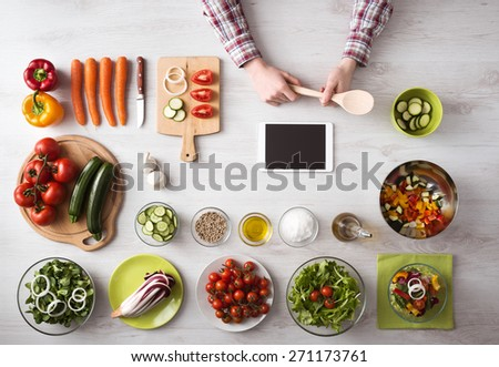 Man's hand cooking at home with touch screen tablet, fresh vegetables and kitchen utensils all around, top view - stock photo