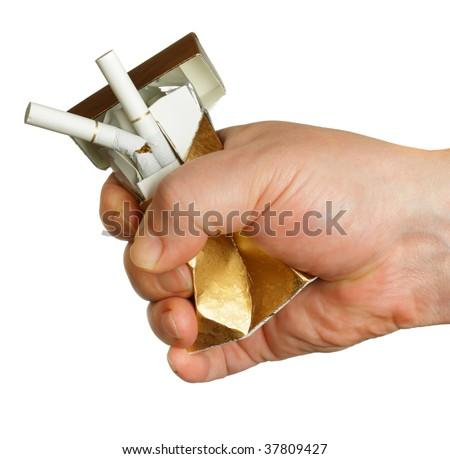 Man's hand crushing cigarette box isolated over white background - stock photo