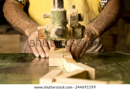 Man's hand detail cutting wood at the industry of the manufacture. - stock photo