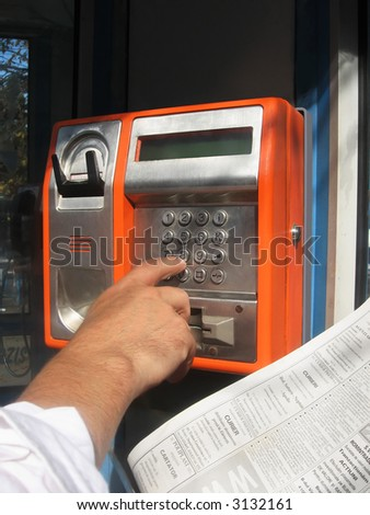 man`s hand dialing on a public phone