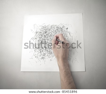 Man's hand drawing on a paper sheet - stock photo