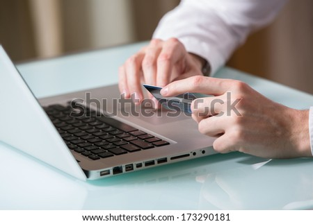 Man's hand entering data using laptop while holding a credit card in the other hand - stock photo
