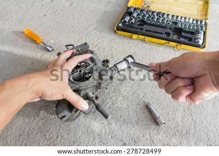 Man's hand fixing car engine carburetor - stock photo