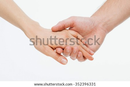 Man's hand gently holding woman's hand - closeup shot - stock photo