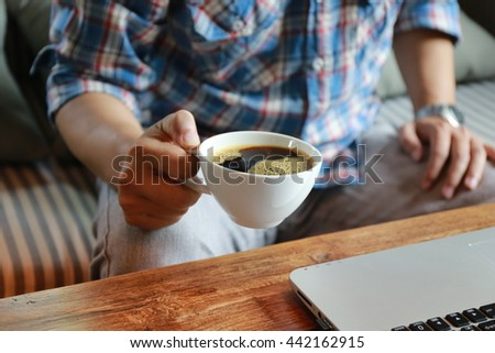 man's hand hold coffee cup and use laptop ,soft focus - stock photo
