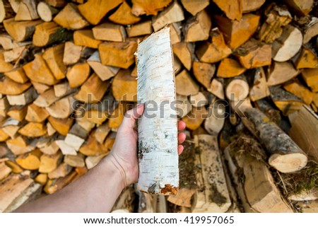 man's hand hold log in the background of the stack of firewood - stock photo