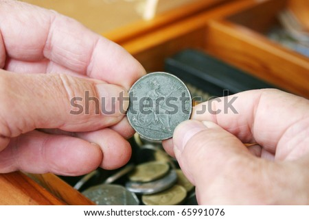 Man's hand holding a 1901 British one penny coin, other old coins in a drawer in the background - stock photo