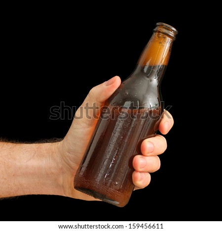Man's Hand holding a Brown Bottle of Beer isolated on black - stock photo