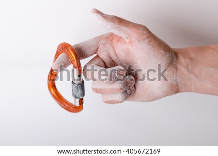Man´s hand holding a carbine on a rope. Climbing equipment isolated on a white background. Hand in powder chalk magnesium.
