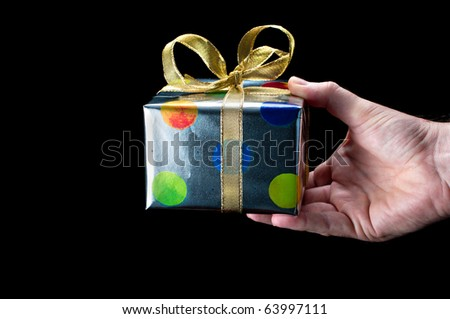 Man's hand holding a colorful silver present with a gold bow on a black background - stock photo