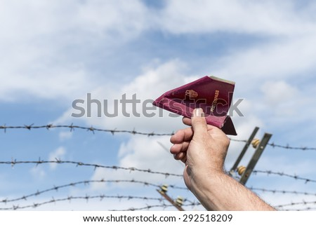man's hand holding a German passport as a paper airplane  over a  barbed wire fence against the blue sky, copy space - stock photo