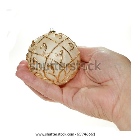 Man's hand holding a gold and white Christmas ornament - stock photo