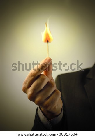 Man's hand holding a match - stock photo