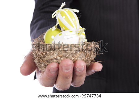 Man's Hand holding a nest with lots of Easter eggs inside