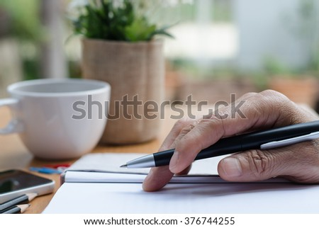Man's hand holding a pen on paper notebook on table in relax position. - stock photo