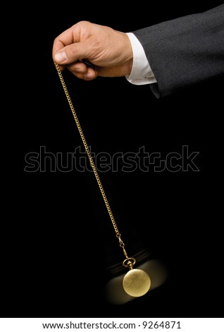 Man's hand holding a pocket watch and swinging it in the fashion of a hypnotist on a black background - stock photo