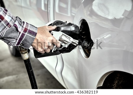 Man's hand holding a Revolver and gas nozzle while  pumping gas into parked vehicle - stock photo
