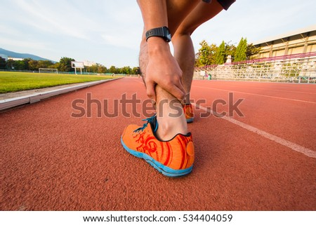 man's hand holding ankle joint pain after running.