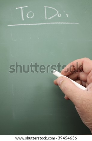 man's hand holding apiece of chalk next to a green chalkboard that states To Do List