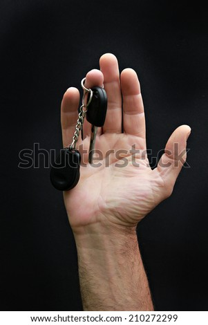 Man's hand holding car key on the black