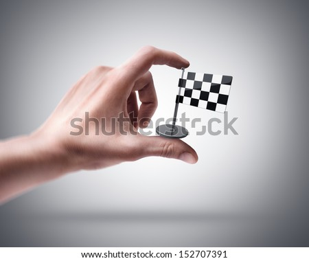 Man's hand holding Checkered Flag