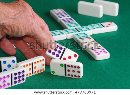 Man's hand holding colorful domino preparing to play in game of Mexican Train.