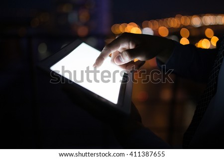 Man's hand holding digital tablet at night city background