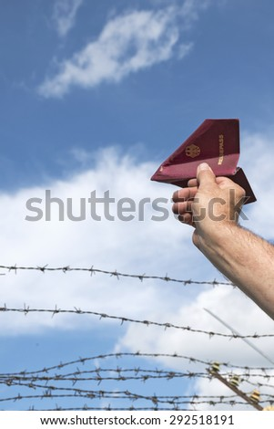 man's hand holding his German passport as a paper airplane high over a  barbed wire fence in the blue sky, copy space - stock photo