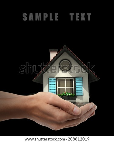 Man's hand holding house isolated on black background. High resolution  - stock photo