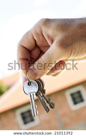 Man's hand holding keys with a house under construction in background - stock photo