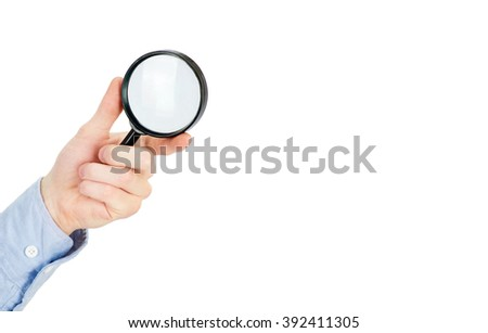 Man's hand holding magnifying glass - stock photo